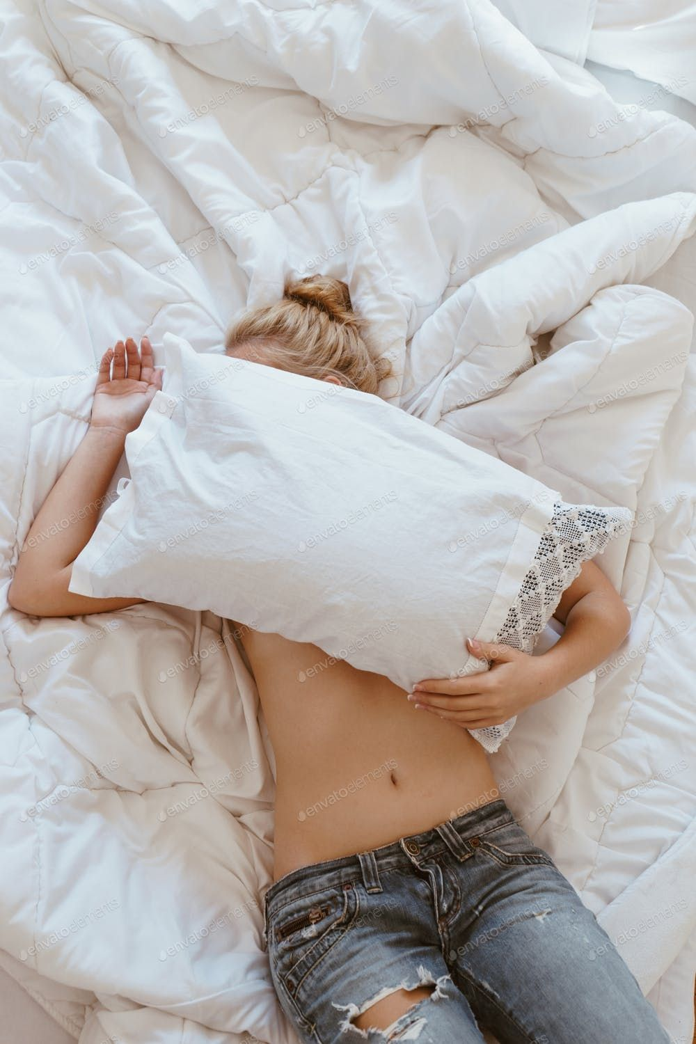 Shirtless woman hiding face with pillow while lying in bed.