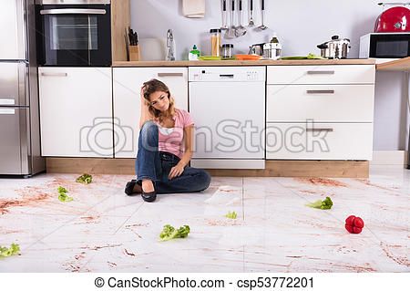 Woman Sitting On Messy Kitchen Floor.