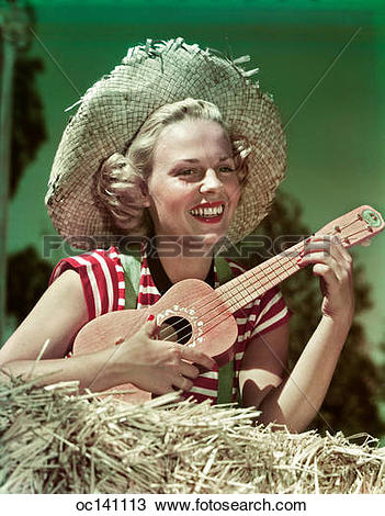 Stock Photo of 1940s 1950s smiling woman wearing straw hat holding.