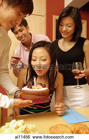 Stock Images of Woman blowing out candle on cake, surrounded by.
