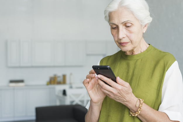 Portrait of senior woman texting on cell phone at home Photo.