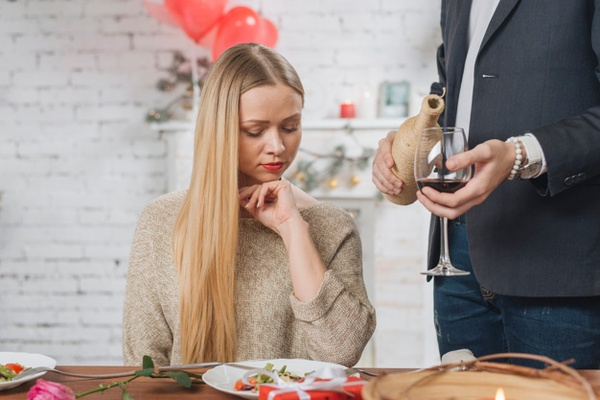 Man serving wine for woman on date.