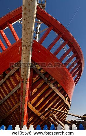 Stock Images of Red wooden boat under construction at the.