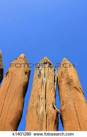 Stock Photography of Pointed tops of a log fence barricade of a.