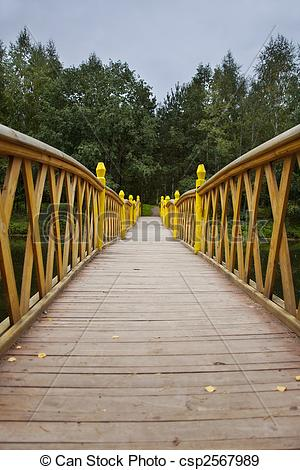Stock Photographs of Wood bridge over water to forest perspective.
