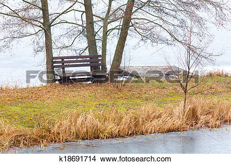 Stock Photo of Rural. Single wooden bench on river bank or lake.