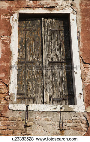 Pictures of Worn building with window with closed wooden shutters.