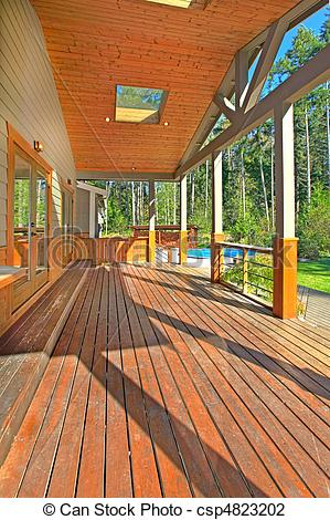Stock Photo of Back porch with wood ceiling in a mountain home.