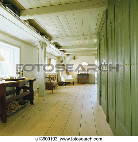 Stock Photo of Stripped wooden floorboards and green wall.