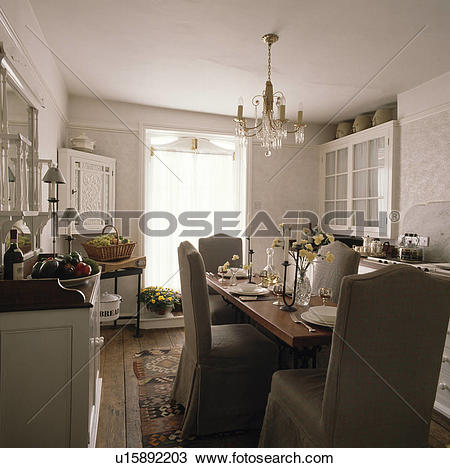 Stock Photo of Glass chandelier above rectangular wooden table and.