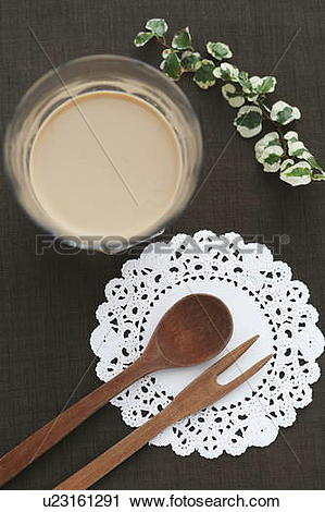 Stock Photography of Glass of coffee and wooden cutlery on paper.