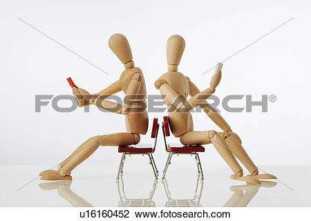 Stock Photo of Wooden figures sitting on chairs back to back.