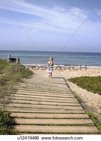 Stock Images of Young boy walking on a wooden path at the beach.