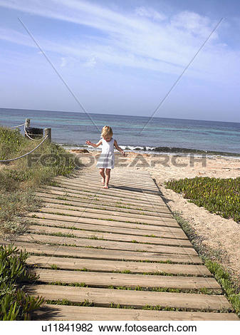 Stock Photo of Young boy walking on a wooden path at the beach.
