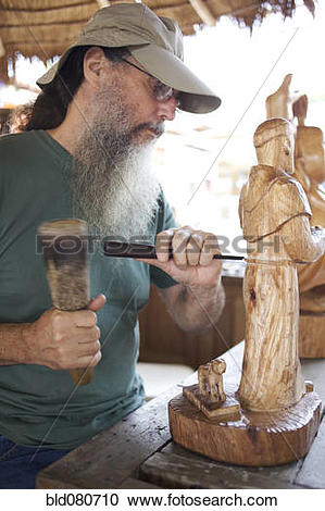 Stock Photography of Mixed race man carving wooden statue.