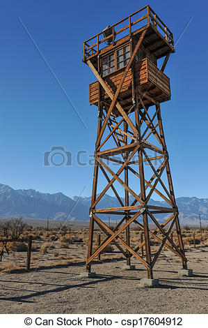 Stock Photography of Wooden guard tower in desert by mountains.