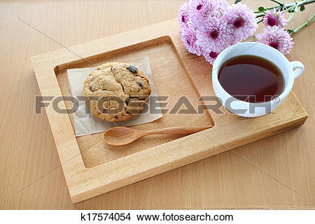Stock Photo of Cup of coffee,cookie and flower on wooden tray.