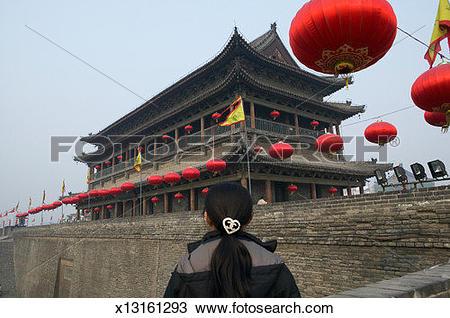 Stock Photo of China, Xian, woman at city wall facing tower, rear.