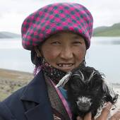 Stock Photograph of Woman holding a lamb at the lakeside, Yamdrok.