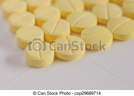 Heap of yellow round medicine tablet.