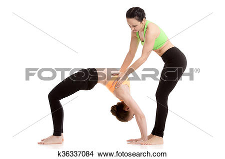 Stock Photo of Instructor assists student in urdhva dhanurasana.
