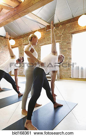 Stock Photography of Instructor assisting student in yoga class.