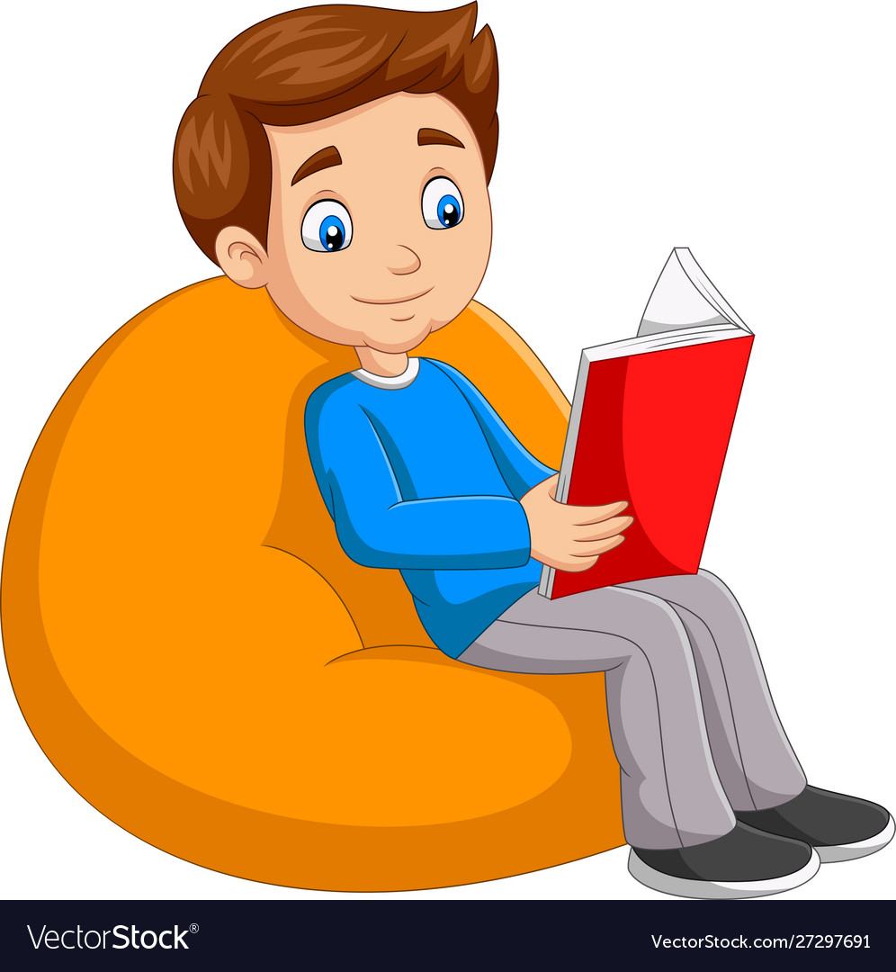 Young boy reading a book sitting on big pillow.