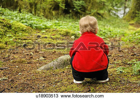 Stock Photo of baby girl child kid young squatting forest floor.