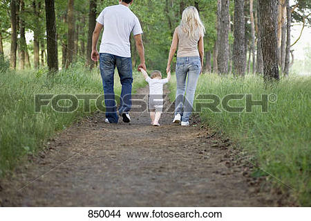 Stock Photo of Two parents walking along a forest path with their.