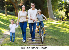 Stock Images of lovely young family walking hand in hand in forest.