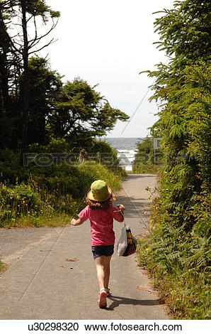 Stock Photography of Young girl walking along path in forest.