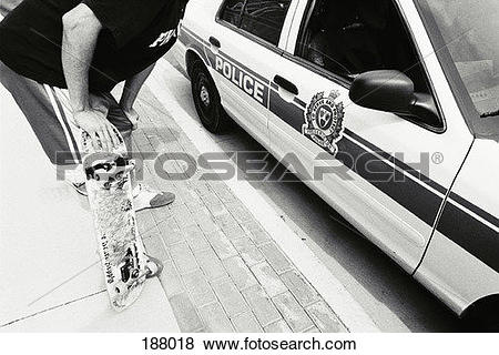 Pictures of Young man with skateboard leaning into police car.