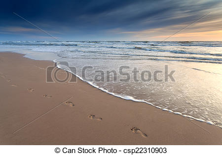 Stock Photography of foot prints on sand beach at sunset.