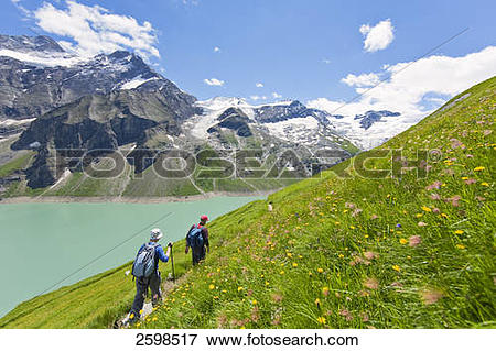 Picture of Hikers walking at lakeside, Hohe Tauern, Alps.