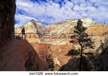Stock Images of Hiker silhouetted on the Hidden Canyon Trail above.